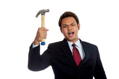 Aggressive Asian businessman angry hold a hammer. Isolated on white background Royalty Free Stock Image