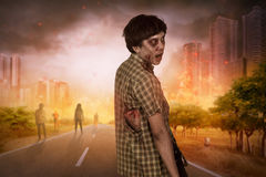 Aggressive asian zombies with blood walking around. On the burning city Stock Image