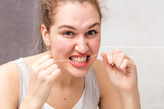 Aggressive beautiful young woman holding a dental floss for hygiene. Aggressive beautiful young woman holding a dental floss caring and cleaning her teeth for Stock Photography