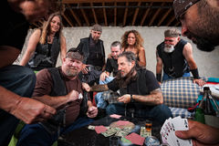 Aggressive Biker Gang Gamblers. Rowdy biker gang gambling and pulling out weapons Stock Photos