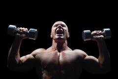 Aggressive bodybuilder lifting bumbbells Royalty Free Stock Photo