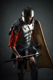 Aggressive brutal warrior attack with a spear. Isolated on gray background Stock Photo