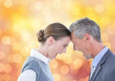 Aggressive business people with head to head screaming over bokeh. Digital composite of Aggressive business people with head to head screaming over bokeh Royalty Free Stock Photo
