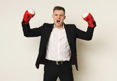 Businessman in red boxing glove punch to the goal. Aggressive businessman in red boxing gloves shouting to camera. Ready to fight in corporate battle, business Stock Images