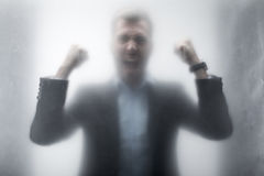 Aggressive businessman in suit screaming behind the glass Royalty Free Stock Photography