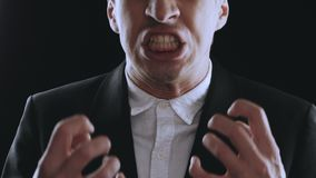 Aggressive businessman in a suit is screaming and showing anger on a black background. Angry boss. The danger of. Angry businessman screaming at white background stock footage