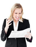 Aggressive businesswoman looking at a newspaper Stock Photos
