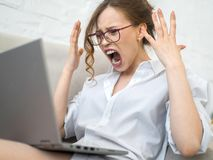 Aggressive career woman. Screaming and frustrated woman with laptop Royalty Free Stock Photos
