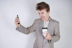 Aggressive caucasian teenager screams into the smart phone and holds a paper cup of coffee in his hand. student on edge on a white. Background in Studio royalty free stock photo