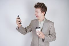 Aggressive caucasian teenager screams into the smart phone and holds a paper cup of coffee in his hand. student on edge on a white. Background in Studio royalty free stock image