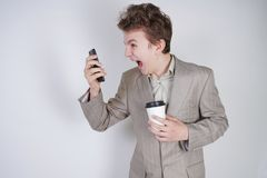 Aggressive caucasian teenager screams into the smart phone and holds a paper cup of coffee in his hand. student on edge on a white. Background in Studio stock images