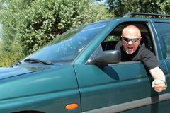 Aggressive driver. With sunglasses, violent driver, in a big car, behind the wheel of violence Royalty Free Stock Photo