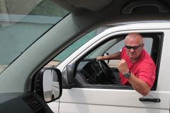 Aggressive driver. With sunglasses, violent driver, in a big car, behind the wheel of violence Royalty Free Stock Images