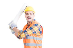 Aggressive engineer concept with furious young male fighting and. Aggressive engineer and violence concept with furious young male fighting with blueprints and Royalty Free Stock Images