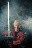 Aggressive fantasy hero with sword in hand royalty free stock images