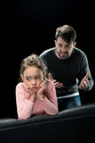 Aggressive father screaming at upset daughter on black Stock Image