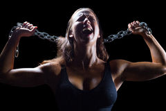 Aggressive female athlete holding chain. Against black background Royalty Free Stock Photo