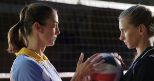 Aggressive female volleyball players looking each other through net 4k. Aggressive female volleyball players looking each other through net at court 4k stock footage
