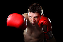 Aggressive fighter man training shadow boxing with red fighting gloves throwing vicious right punch Royalty Free Stock Photography