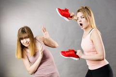 Aggressive Frauen, die unter Verwendung der Schuhe mit Frau kämpfen Lizenzfreie Stockfotografie