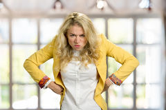 Aggressive frowning young blonde woman. Frustrated european woman in formal wear holding hands on hips with negative emotions, blurred background Royalty Free Stock Photo