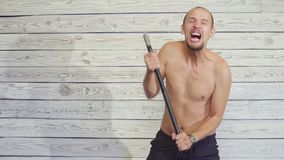 Aggressive but funny maniac killer with an ax indoors. Aggressive maniac killer with an ax indoors stock footage