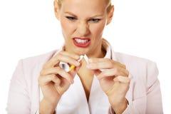 Aggressive Geschäftsfrau, die Zigarette bricht stockbilder