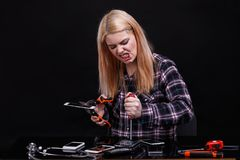 Aggressive girl, angrily breaks smartphones with the help of tools. On a black background. Royalty Free Stock Photos
