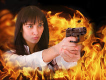 Aggressive girl shoots from flame. Stock Image