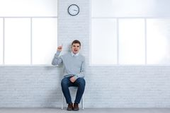 An aggressive guy, sits on a chair and angrily screams showing a thumbs-up. Royalty Free Stock Photography
