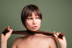 Aggressive hostile angry emotion woman portrait. Aggressive pretty woman. Hostile facial expression. Closeup portrait of emotional lady pulling aside hair royalty free stock photography