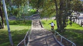 Aggressive inline roller blader grind on rail in skatepark outside. Clip. Summer extreme sport exercising outdoor in. Aggressive inline roller blader grind on Stock Photo