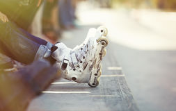 Aggressive inline rollerblader sitting in outdoor skate park Royalty Free Stock Image