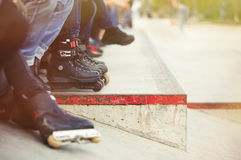 Aggressive inline rollerblader sitting in outdoor skate park Stock Photos