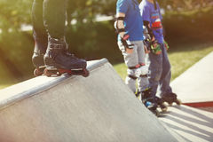 Aggressive inline rollerblader standing on ramp in skatepark Stock Images