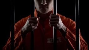 Aggressive inmate holding prison bars, unfairly judged, court sentence appeal stock photos