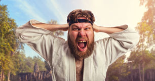Aggressive karateka. Is tightening the black belt on his head Stock Images