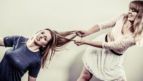 Aggressive mad women fighting each other. Aggressive mad women fighting each other pulling hair. Two young girls struggling win catfight. Violence Stock Image