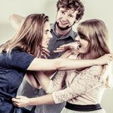 Aggressive mad women fighting over man. Young jealous girls wooing guy. Violence Royalty Free Stock Image