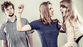 Aggressive mad women fighting over man. Jealous girls wooing guy. Violence Stock Photography