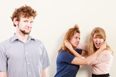 Aggressive mad women fighting over man. Jealous girls wooing guy. Violence Royalty Free Stock Photo