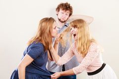 Aggressive mad women fighting over man. Jealous girls wooing guy. Violence Royalty Free Stock Image