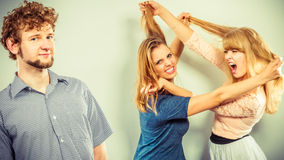 Aggressive mad women fighting over man. Royalty Free Stock Photography