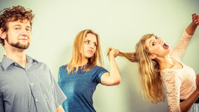 Aggressive mad women fighting over man. Stock Photos