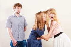 Aggressive mad women fighting over man. Aggressive mad women fighting over men pulling hair. Young jealous girls wooing guy. Violence Stock Images