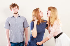 Aggressive mad women fighting over man. Stock Photo