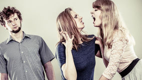 Aggressive mad women fighting over man. Young jealous girls wooing guy. Violence Royalty Free Stock Photos