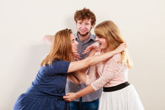 Aggressive mad women fighting over man. Young jealous girls wooing guy. Violence Stock Image