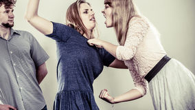 Aggressive mad women fighting over man. Young jealous girls wooing guy. Violence Stock Photos