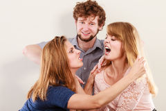 Aggressive mad women fighting over man. Young jealous girls wooing guy. Violence Stock Images